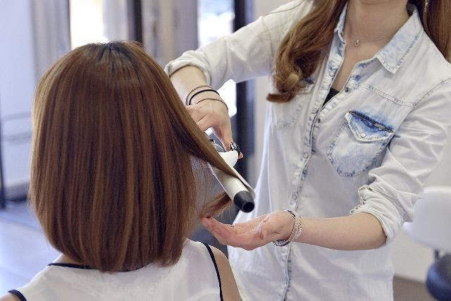 コテを使って、髪を伸ばしてもらっている女性